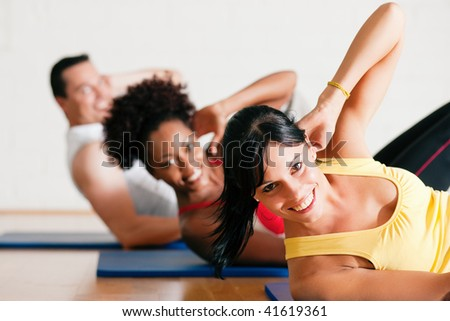 Group of three people exercising doing sit-ups in the gym - stock photo