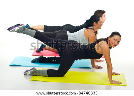 Group of three people flexing their legs in a fitness club - stock photo