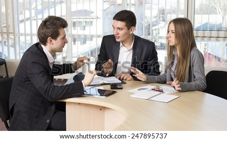 Group of three people having discussion.  Business people tries to convince each other making eloquent gestures - stock photo