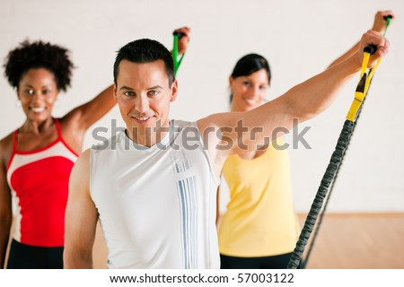 Group of three people in colorful cloths in a gym doing gymnastics with tube equipment - stock photo
