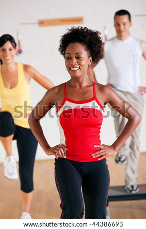 Group of three people in colorful cloths in a gym doing step gymnastics, a female instructor in front - stock photo