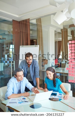 Group of three successful business partners in casual looking at laptop screen and listening to young man explanations at meeting in office - stock photo