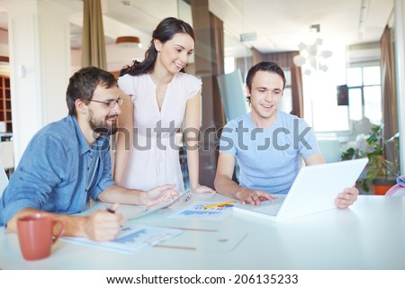 Group of three successful business partners in casual working at meeting in office - stock photo