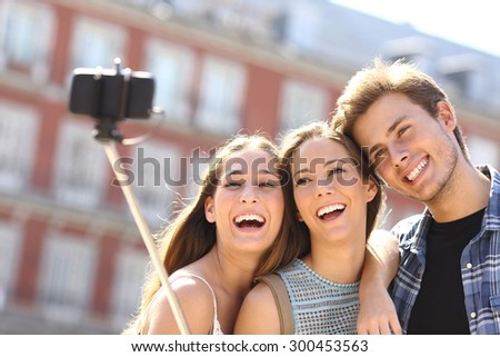 Group of three tourist friends taking selfie with smart phone hand hold monopod in the street - stock photo