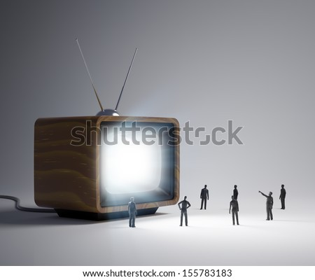 Group of tiny people watching a TV program in vintage television set - stock photo