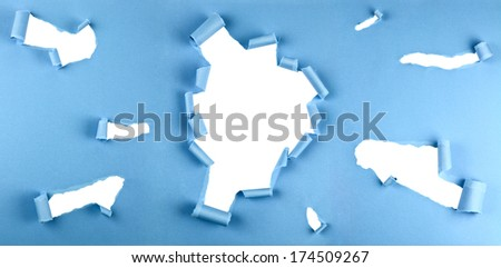Group of torn holes in blue paper isolated over a white background - stock photo