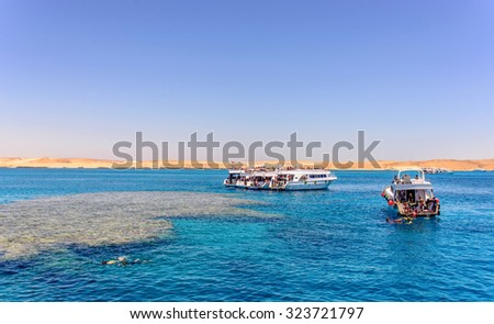 Group of tour ships and dive boats moored off an offshore reef and sand bar in a calm blue tropical ocean on a hot summer day - stock photo