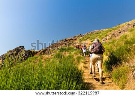Group of tourists climbing in mountains, Portugal, Madeira - stock photo