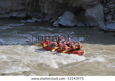 Group of tourists fighting with strong stream of mountain river. - stock photo