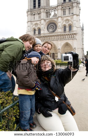 Group of tourists, members of one family taking self portrait at the famous Cathedrale Notre-Dame de Paris - stock photo