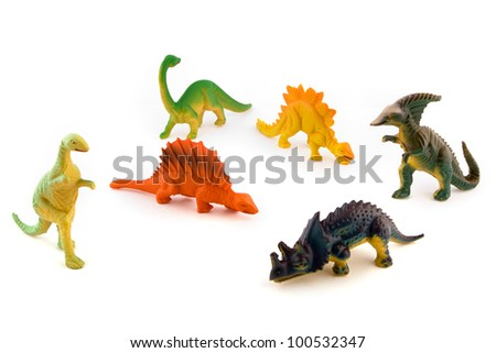 Group of toy plastic dinosaurs over white - stock photo