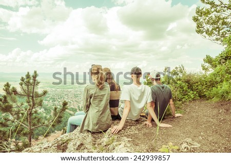 Group of traveling friends sitting together on the edge of a cliff and watching the peaceful landscape. Tourists visiting Brasov, Romania with a retro vintage instagram look - stock photo
