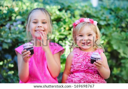 group of two children cute fashion little girls eat happy birthday pink cupcake - stock photo