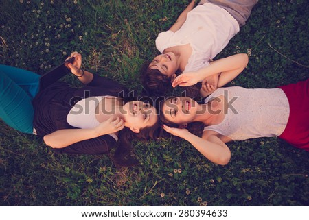 Group of two young woman and child lying on the grass and having fun - stock photo