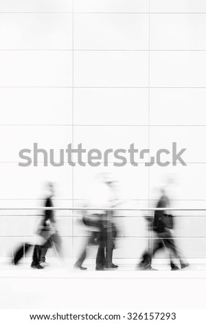 Group of unrecognizable business people in front of modern architecture, blurred motion, black and white photo - stock photo