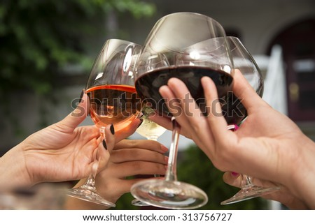 Group of unrecognizable people celebrating while holding wine glasses and toasting. - stock photo