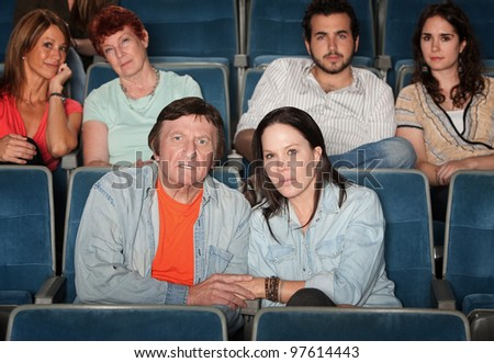 Group of upset audience watch movie in theater - stock photo