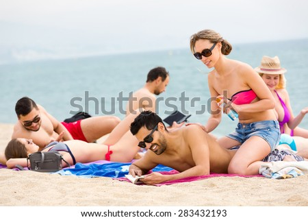 Group of vacationers sunbathing on a sunny beach on a shore of an ocean - stock photo