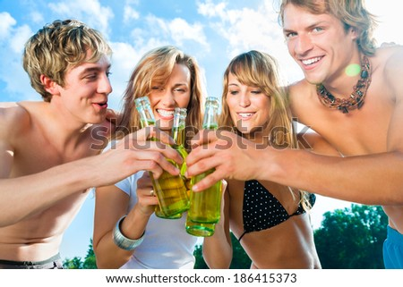 Group of very beautiful people celebrating on the beach in the summer of their lives - stock photo