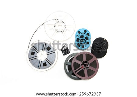 Group of vintage 8mm  reels different size and colors around little clapper board isolated on white background - stock photo
