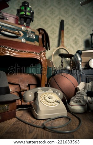 Group of vintage objects on attic hardwood floor, including old toys, phone and sports items. - stock photo
