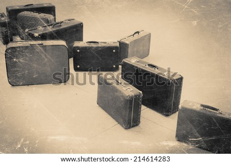 group of vintage suitcase on tiled floor, retro stylized in black and white color photo - stock photo