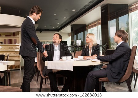 Group of well dressed business people greeting  handsome businessman. Looking and shaking hands at restaurant  - stock photo
