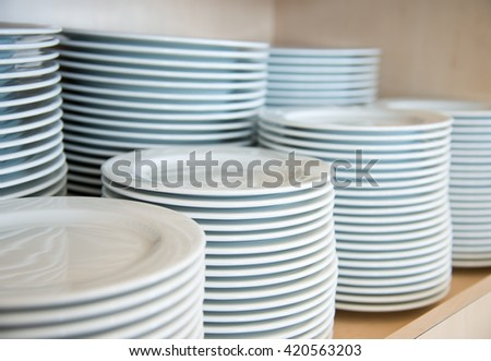Group of white plates stacked together in a hotel. - stock photo