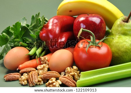 Group of wholesome, organic food, including pear, apple, tomato, eggs, nuts, pecans, walnuts, carrot, banana, and apple, for a healthy diet or slimming New Year resolution. - stock photo