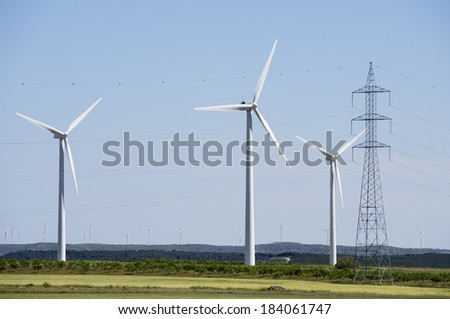 group of windmills for renewable electric energy production and pylon - stock photo