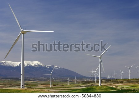 group of windmills in an idyllic green meadows - stock photo