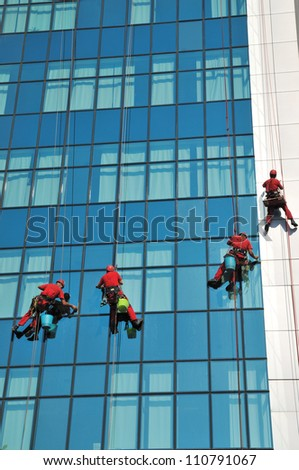 Group of windows washer cleaning the high building glass - stock photo