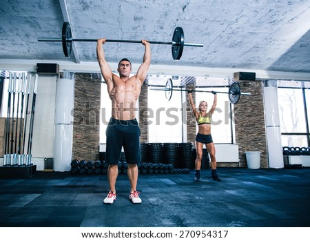 Group of woman and man workout with barbell at gym - stock photo