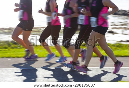 Group of woman compete in the race on coastal road. Blurred motion - stock photo