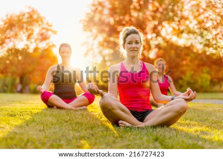 group of 3 women doing yoga in nature - stock photo