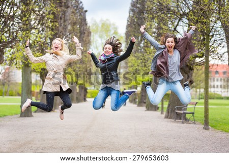 Group of women jumping at park in Copenhagen. They are in their twenties and they are wearing smart casual clothes. Happiness, friendship and success concepts. - stock photo