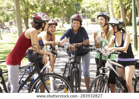 Group Of Women Resting During Cycle Ride Through Park - stock photo
