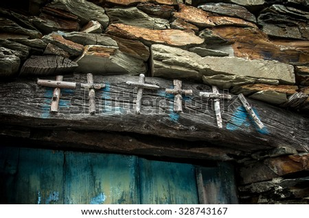 Group of wooden crosses over rural house door to protect harvest - stock photo