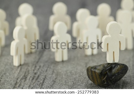Group of wooden figures and one figure in the foreground as a model or speakers, may, in Network Marketing - stock photo