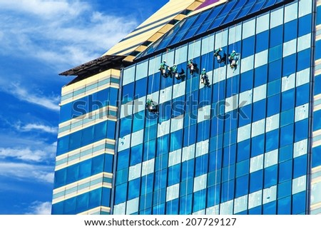 Group of Workers Cleaning Windows Service on High Rise Building. - stock photo