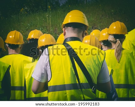 Group of workers in hardhats. View from the back. - stock photo