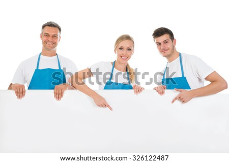 Group Of Workers Showing Blank Billboard Over White Background - stock photo