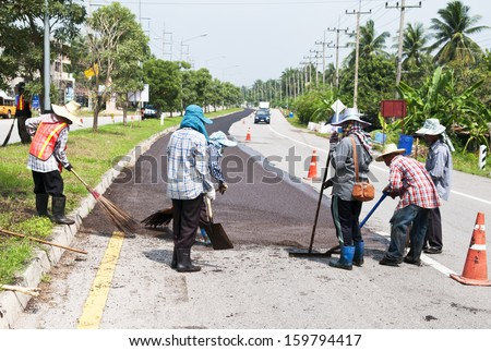 Group of workers working on Asphalt paving  on road renovation  - stock photo