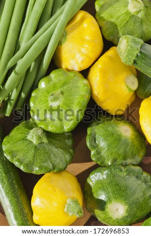 Group of yellow and green pattypan squashes with string green beans, fresh vegetables concept image - stock photo