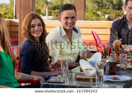 Group of young adults eating out and drinking at a restaurant outdoors - stock photo