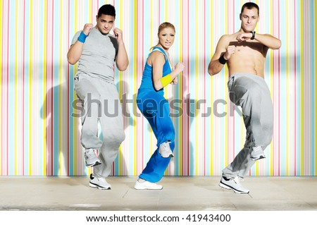 group of young adults exercise in fitness club with trainer - stock photo