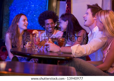 Group of young adults in a nightclub talking and laughing - stock photo