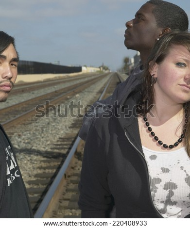 Group of young adults standing on railroad tracks - stock photo
