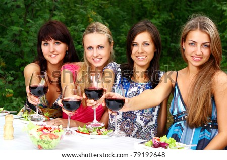 Group of young and beautiful women drink wine in the park - stock photo