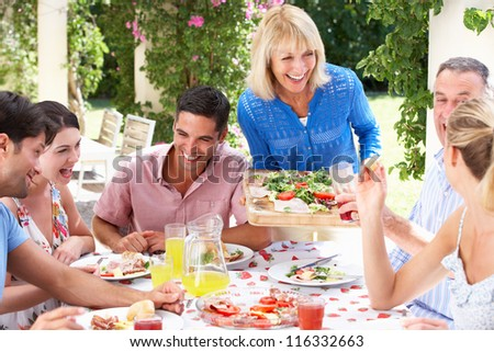 Group Of Young And Senior Couples Enjoying Family Meal - stock photo
